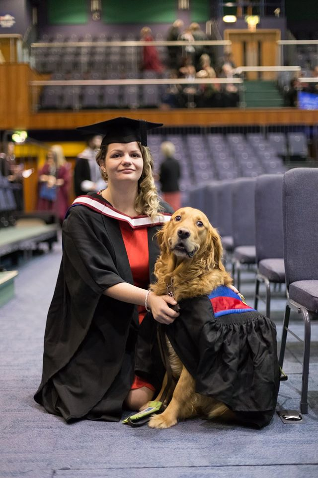 Owner And Dog Graduates In Full Graduation Cap And Gown